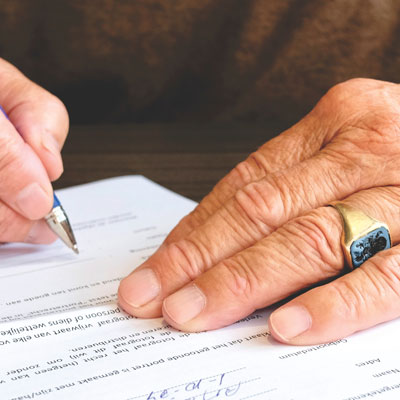 Elderly man signing papers