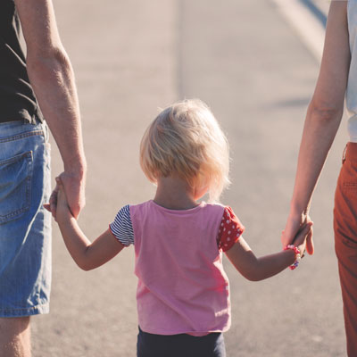 Image of child holding parent's hands